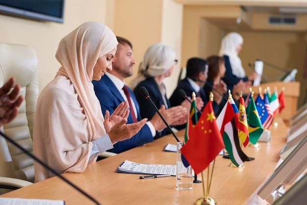 Groep hedendaagse interculturele afgevaardigden die in de handen klappen voor een van de sprekers na het maken van een verslag op de conferentie