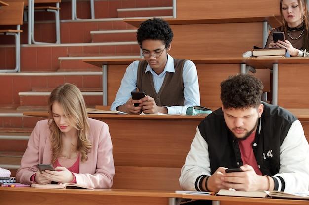 Groep hedendaagse jonge interculturele studenten in vrijetijdskleding die bij de bureaus in de collegezaal zitten en tijdens de pauze op smartphones scrollen