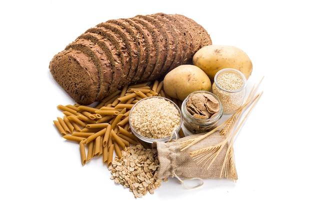Groep hele voedingsmiddelen complexe koolhydraten geïsoleerd op een witte achtergrond
