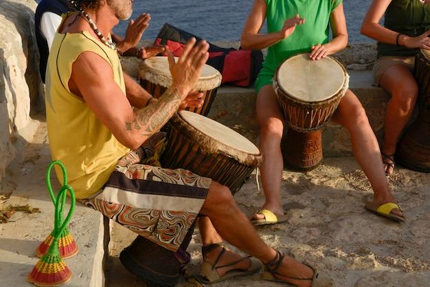 Groep hippies die drummen