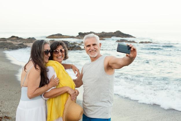 Groep hogere vrienden die selfie met smartphone op het strand nemen