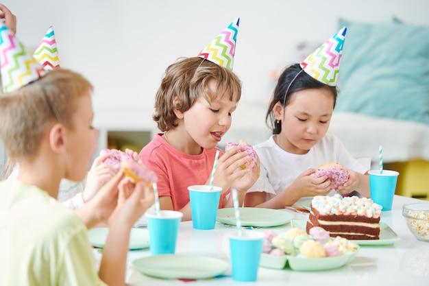 Groep hongerige kleine kinderen die geglazuurde donuts met hagelslag eten en drankjes drinken terwijl ze aan de verjaardagstafel zitten