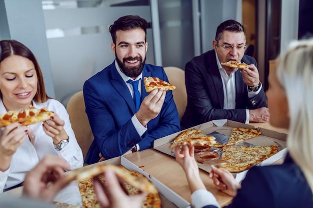 Groep hongerige zakenmensen met pizza voor de lunch zittend in de directiekamer.