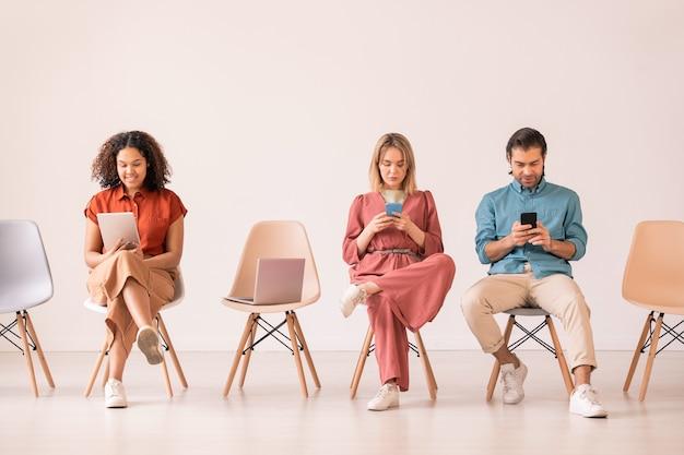 Groep interculturele millennials in vrijetijdskleding zittend op witte stoelen in rij en scrollen in hun smartphones en digitale tablet