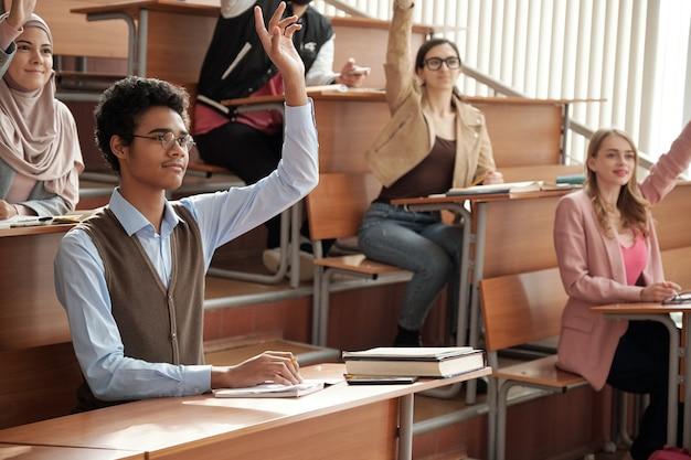 Groep interculturele studenten die handen opsteken bij les
