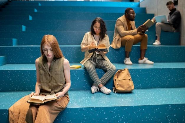 Groep interculturele studenten die op blauwe trap zitten en lezen