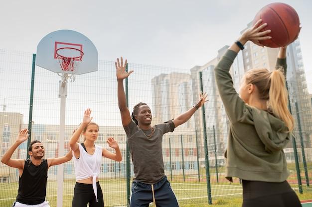 Groep interculturele studenten of vrienden in sportkleding basketballen op speelplaats in stedelijke omgeving