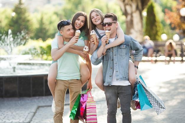 Groep jonge aantrekkelijke mensen die het winkelen maken. vrienden die in openlucht het winkelen houden zakken en het glimlachen. vrolijke vrienden samen.