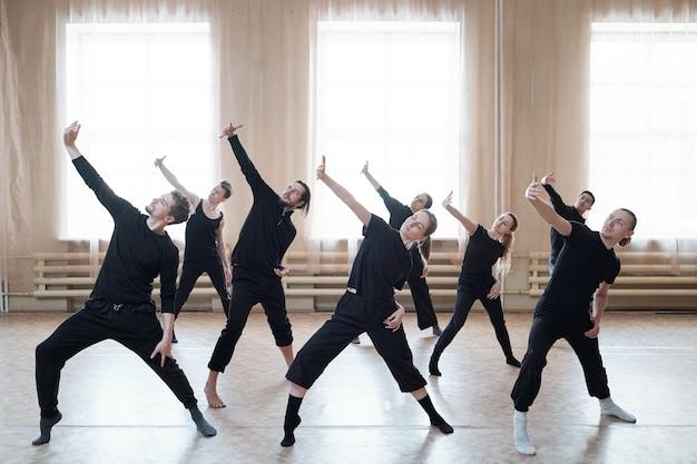 Groep jonge actieve dansers in zwarte t-shirts en broeken die een arm voor zich uitrekken tijdens dansoefening