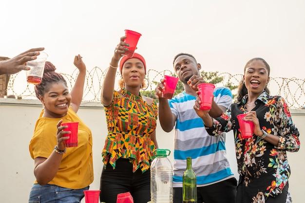 Groep jonge afrikaanse vrienden die een feestje hebben, een toast uitbrengen, dansen en plezier hebben