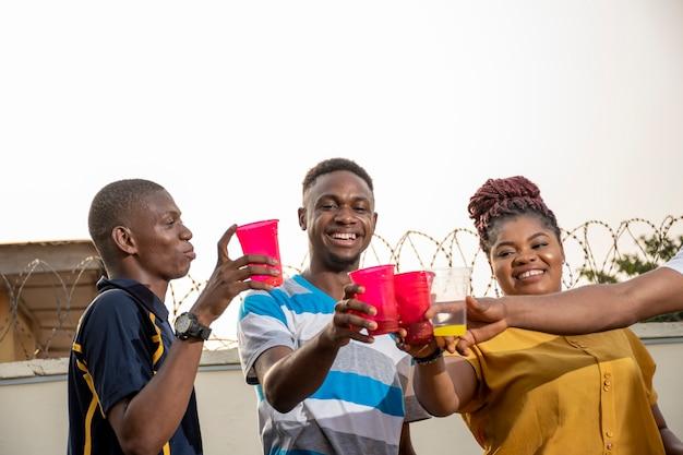 Groep jonge afrikaanse vrienden die een feestje hebben, proosten