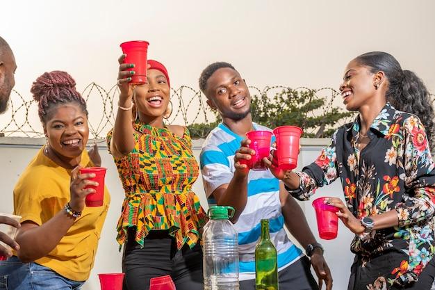 Groep jonge afrikaanse vrienden die samenkomen, een toast uitbrengen, dansen en plezier hebben