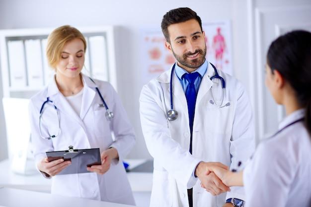 Groep jonge artsen in het ziekenhuis communiceren en handen schudden