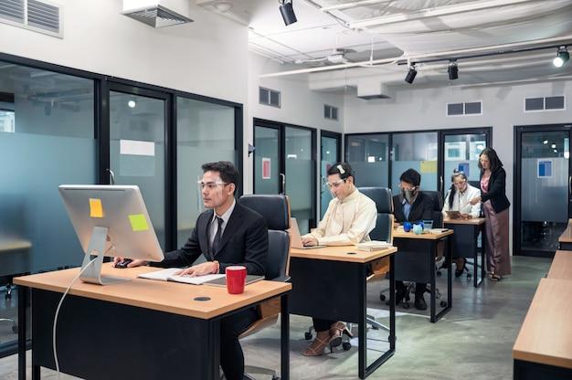 Groep jonge aziatische collega's die met laptop aan bureau in modern bureau werken