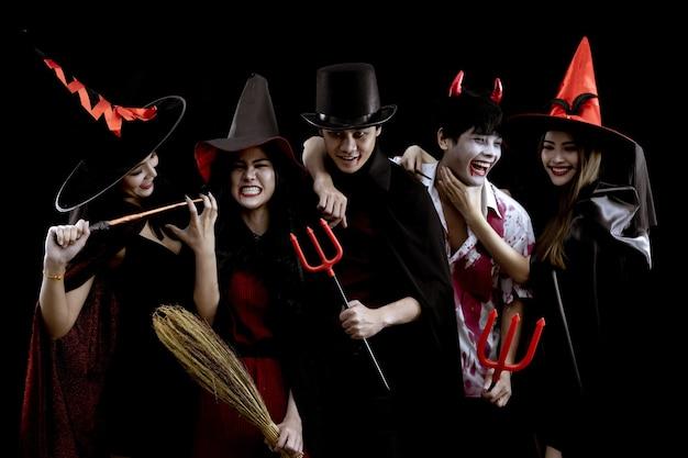 Groep jonge aziatische in kostuum halloween-feest op zwarte muur met concept voor halloween-modefestival. bende van aziatische tiener in cosplay halloween. kostuumgeest, kwaad van thaise groepstiener.