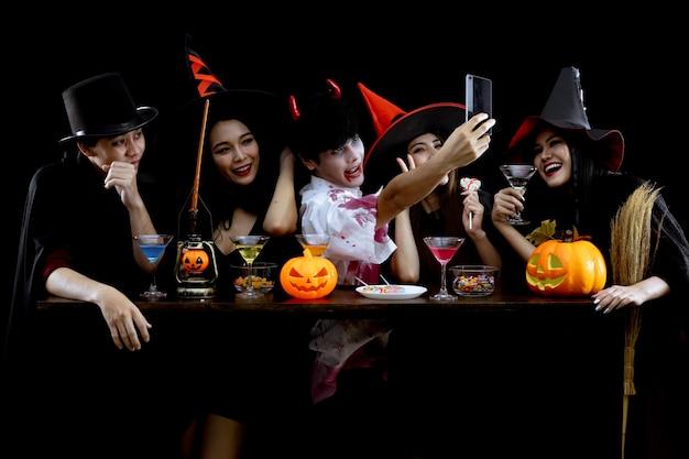 Groep jonge aziatische in kostuum vieren halloween-feest en selfie op zwarte achtergrond. bende tiener aziatische in cosplay halloween. kostuumspook, kwaad van groep tiener thai met plezier. Premium Foto