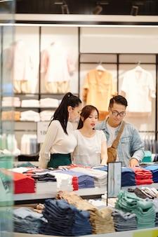 Groep jonge aziatische mensen die voor nieuwe kleren in afdeling van winkelcomplex winkelen
