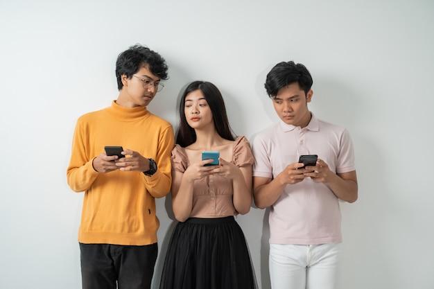Groep jonge aziatische vrienden gluurt naar elkaar terwijl ze hun smartphones gebruiken