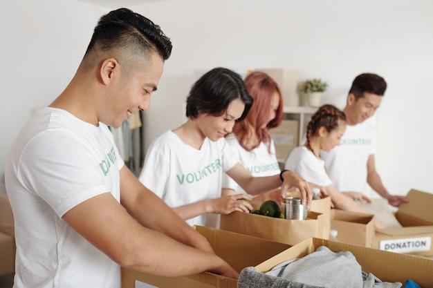 Groep jonge aziatische vrijwilligers die voedsel en kleding in kartonnen dozen inpakken om het aan mensen in nood of vluchtelingen te geven