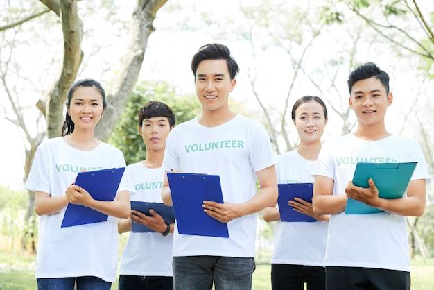 Groep jonge aziatische vrijwilligers die zich in openlucht bevinden