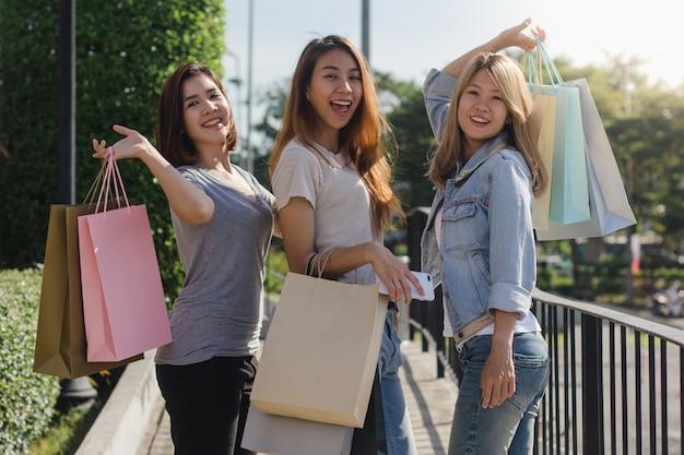 Groep jonge aziatische vrouw die in een openluchtmarkt met het winkelen zakken in hun handen winkelt