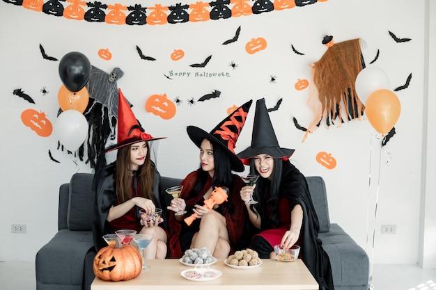 Groep jonge aziatische vrouwen in kostuumheks vieren feest in de kamer voor thema halloween thuis. gang tiener thai met halloween-feest vieren met een glimlach. concept partij halloween thuis.
