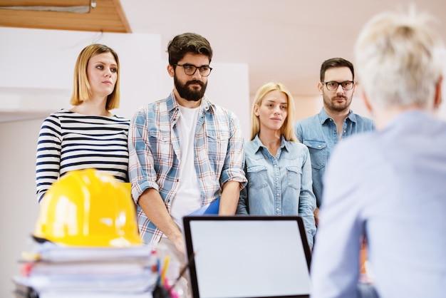 Groep jonge bang collega's wachten in de rij met mappen op een reactie van de vrouwelijke baas.
