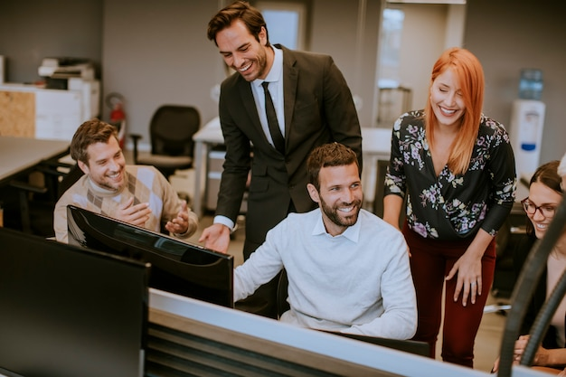 Groep jonge bedrijfsmensen die en in creatief bureau samenwerken communiceren