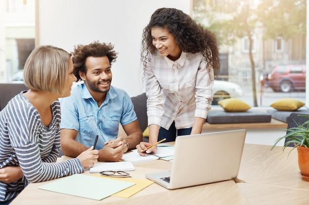 Groep jonge bedrijfsmensen die productieve ochtend in bibliotheek doorbrengen, bedrijfsplannen bespreken en bedrijfsstrategie ontwikkelen. bedrijfsconcept