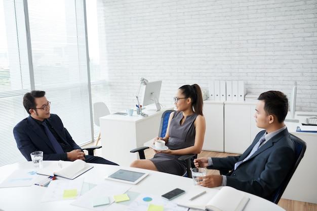 Groep jonge bedrijfsmensen die zitting bij bureau werken
