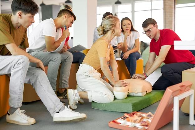Groep jonge blanke mensen die leren hoe ze een leven kunnen redden door samen te zitten Premium Foto