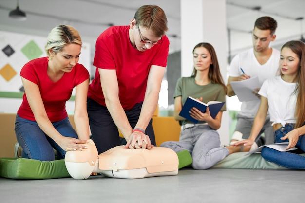 Groep jonge blanke mensen die leren hoe ze een leven kunnen redden door samen te zitten