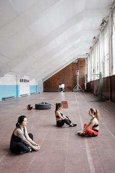 Groep jonge blanke vrouwen in sportkleding hun benen strekken na training zittend op de vloer in ruime sportschool