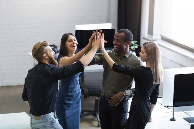 Groep jonge collega's geven elkaar een high five