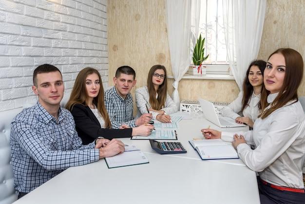Groep jonge consultants in kantoor wijzend op belastingformulier 1040