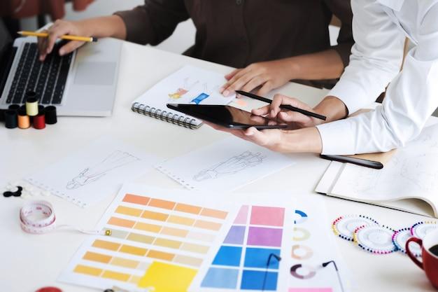 Groep jonge creatieve modeontwerpers werken hard aan project in een studio