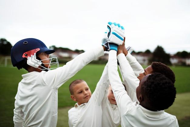 Groep jonge cricketers die een hoogte vijf doen