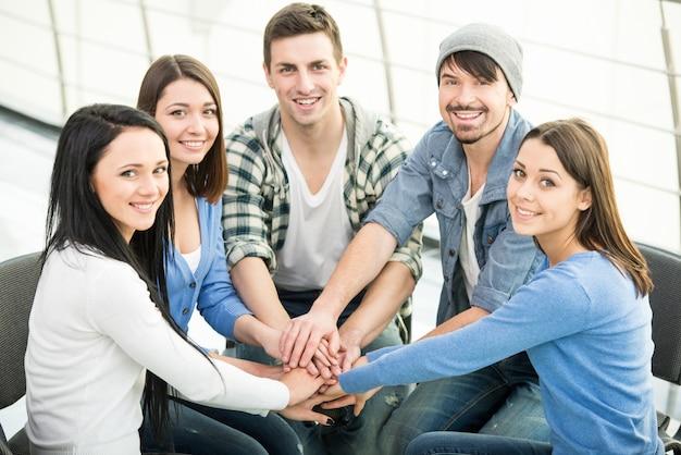 Groep jonge en diverse mensen slaan de handen ineen.