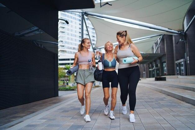 Groep jonge en oude vrouwen die na het sporten buiten in de stad lopen, praten