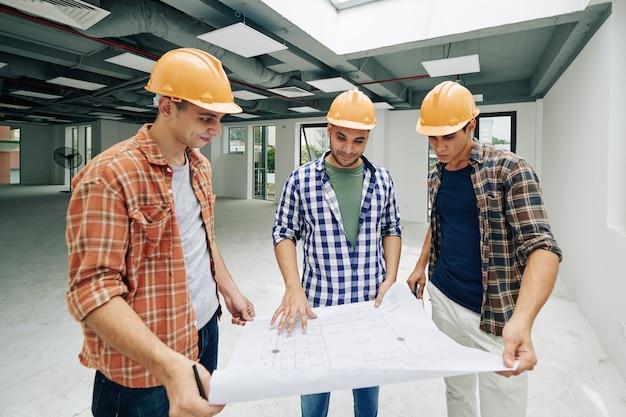 Groep jonge glimlachende bouwvakkers die vlakte van bouw controleren en werk verdelen