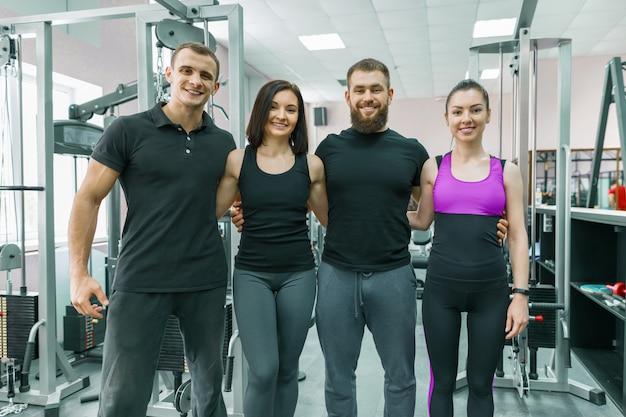 Groep jonge glimlachende sportmensen die samen omhelzen