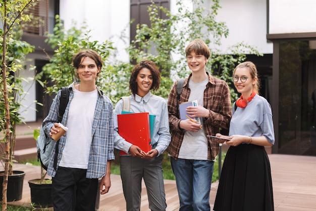 Groep jonge glimlachende studenten die zich met boeken en omslagen in handen en gelukkig bevinden
