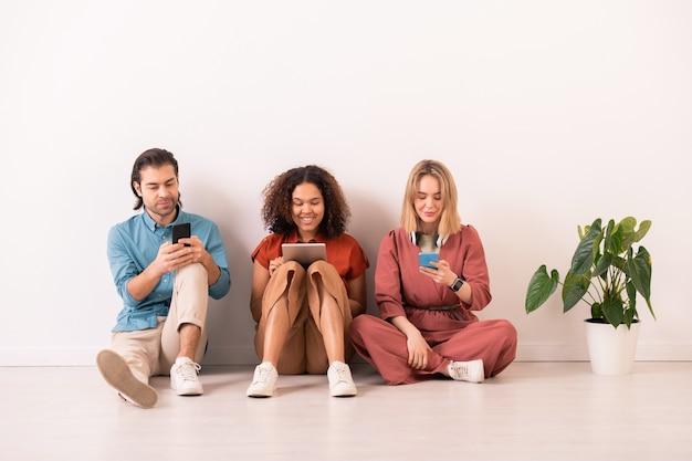 Groep jonge hedendaagse millennials zittend op de vloer tegen de muur en op hun gemak scrollen in smartphones en touchpad
