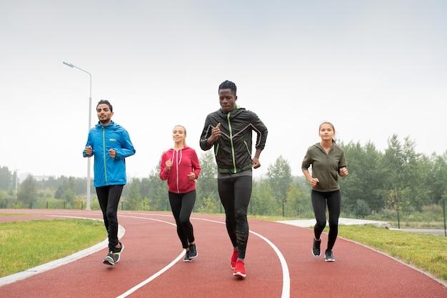 Groep jonge interculturele sporters en sportvrouwen die deelnemen aan de marathon- of sprintwedstrijd op het stadion