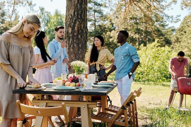 Groep jonge internationale vrienden in vrijetijdskleding praten door geserveerd tafel onder dennenboom terwijl blond meisje vers brood snijden voor het diner