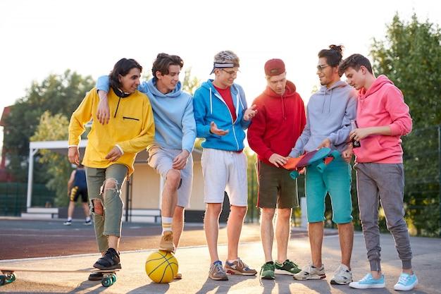 Groep jonge jongens bespreken nieuw skateboard in handen