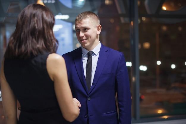 Groep jonge kantoormanagers vieren de succesvolle afronding van de transactie man schudt de hand met een zakenvrouw teamwerk deadlines dringende bestelling