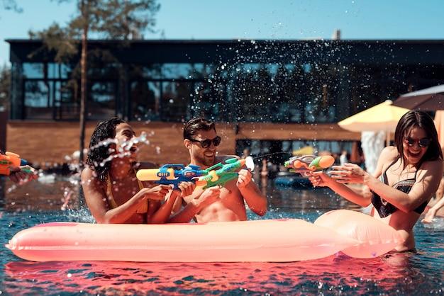 Groep jonge lachende vrienden met plezier in zwembad