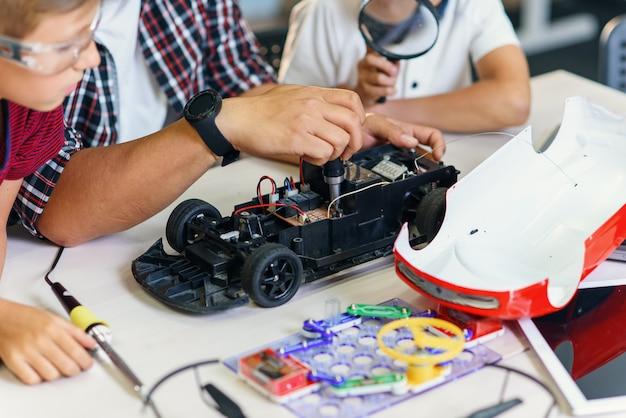 Groep jonge mannelijke leerlingen met aziatische wetenschapper reparatie radiografisch bestuurbaar automodel.