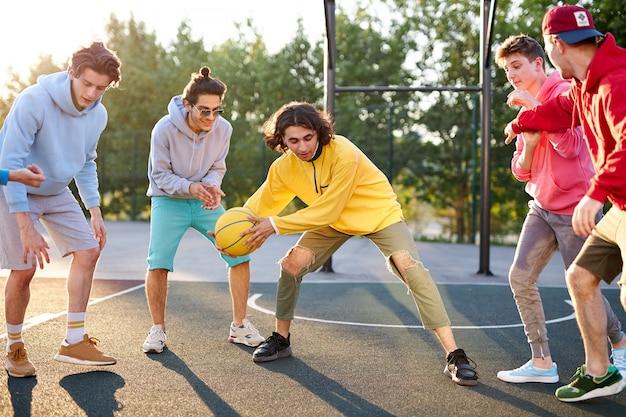 Groep jonge mannelijke tieners in kleurrijke hoodies die basketbal buiten in de straat spelen